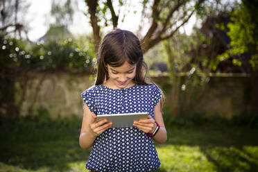 Smiling girl standing in the garden using digital tablet - LVF08872