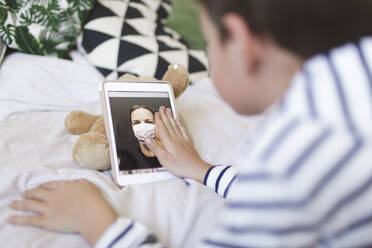 Boy lying on bed having video call on digital tablet with his mother wearing protective mask - HMEF00925