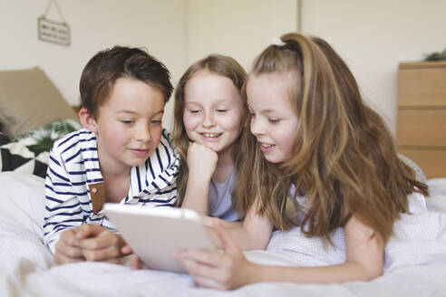 Portrait of boy and his two sisters lying on bed using digital tablet for homeschooling - HMEF00928