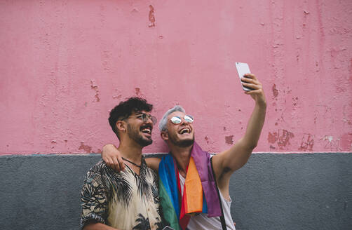 Gay couple taking a selfie in front of pink and grey wall - JCMF00724