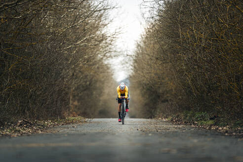 Young sportsperson riding bicycle on road amidst bare trees - MTBF00400
