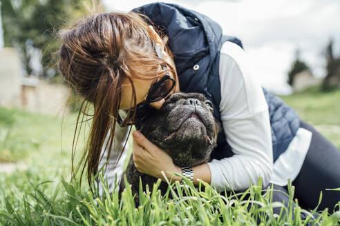 Woman cuddling her bulldog on a meadow - OCMF01214