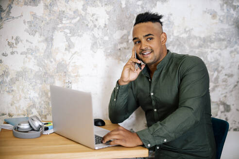 Portrait of young man on the phone working at home office - DAWF01476