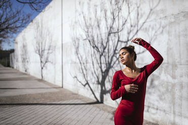 Woman in red dress with dancer pose and tree shadows on  wall - TCEF00621