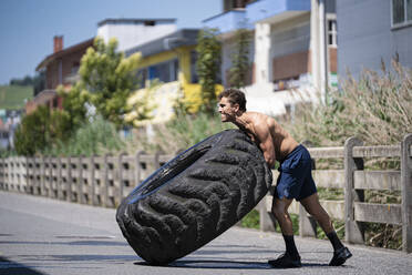 Athlete with an amputated arm exercising with tractor tire on a road - SNF00187
