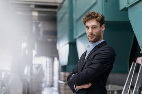 Portrait of a confident young businessman in a factory - DIGF10679