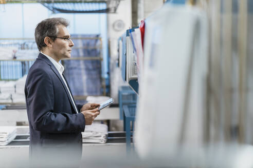 Mature businessman holding tablet in a factory - DIGF10730