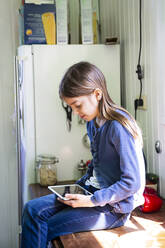 Girl sitting on worktop in the kitchen looking at digital tablet - LVF08875
