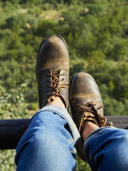 Man wearing old leather shoes, partial view - VEGF02159