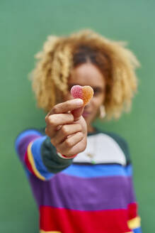 Young woman holding candy heart while standing against green wall - VEGF02176