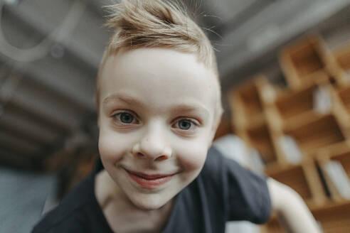 Close-up portrait of smiling blond boy at home - OGF00403