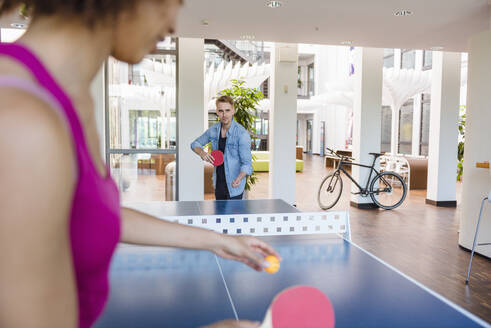 Young business people plaing table tennis in loft office - DIGF10852
