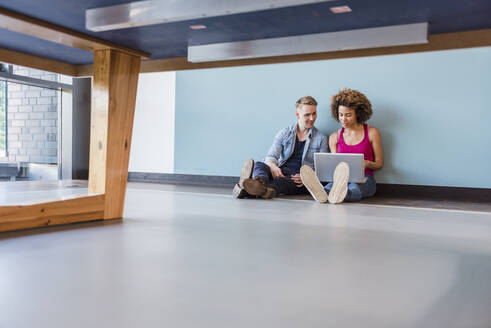 Young woman and man sitting on floor in modern office, using laptop - DIGF10858