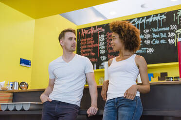 Young businessman and woman talking in office cafeteria - DIGF10873