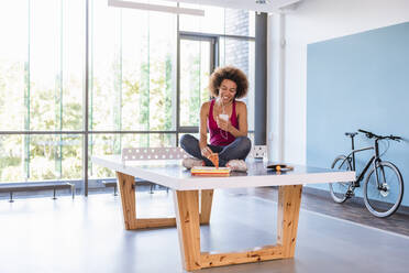 Young woman sitting on ping pong table, eating pizza, using smartphone and earphones - DIGF10876