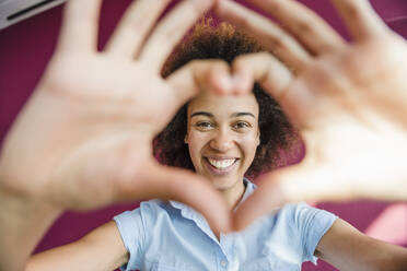Laughing young woman looking through heart-shape finger frame - DIGF10885