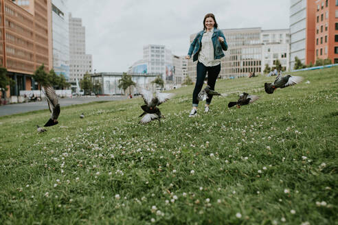 Germany, Berlin, Young woman running on grass surprising flock of pigeons - VBF00040