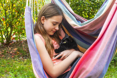 Portrait of girl in hammock cuddling cat - SARF04577