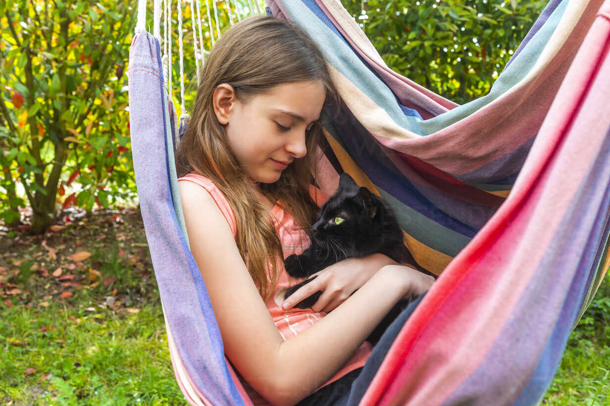 Portrait of girl in hammock cuddling cat - SARF04577 - Sandra Roesch/Westend61