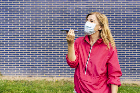 Woman with surgical mask using smartphone - DGOF00997