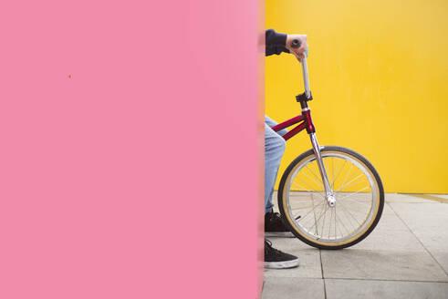 Teenage boy on BMX bike hiding behind pink wall - JCMF00743