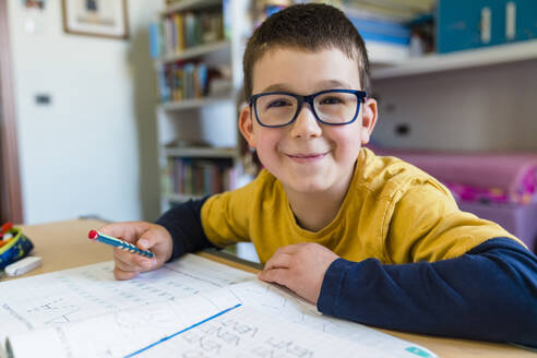Smiling cute boy sitting with book at desk during COVID-19 homeschooling - MGIF00940