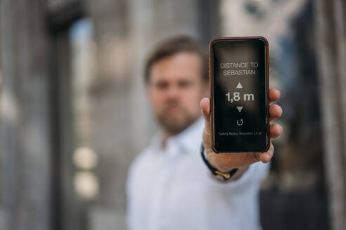 Close-up of man holding smartphone showing distance on display - JOSEF00570
