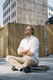 Businessman sitting on skateboard at construction site in the city with closed eyes - JOSEF00582