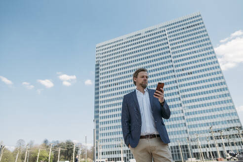 Businessman using smartphone in the city - JOSEF00603