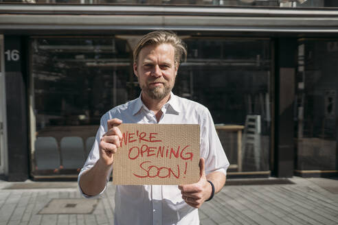 Shopkeeper holding cardboard with opening announcement in the city - JOSEF00618