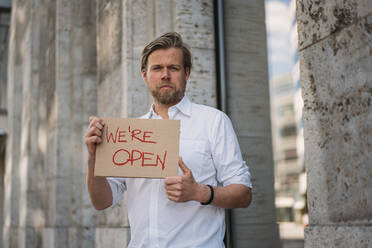 Shopkeeper holding cardboard with opening announcement in the city - JOSEF00633