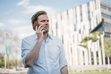Portrait of businessman on the phone in the city - JOSEF00648