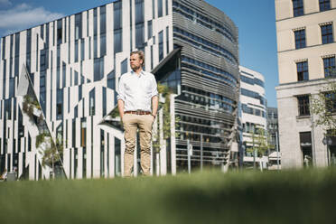 Businessman standing in grass in the city - JOSEF00651