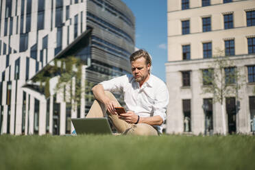 Businessman with laptop sitting in grass in the city using smartphone - JOSEF00654