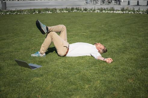 Businessman lying in grass next to laptop - JOSEF00657