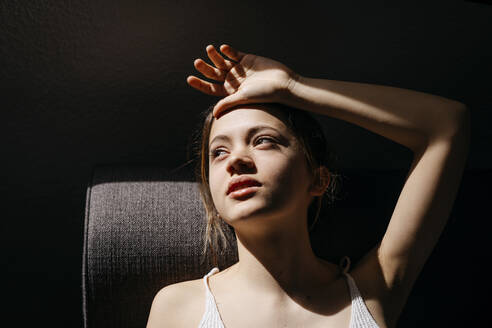 High angle view of thoughtful young woman lying on sofa at home - TCEF00643