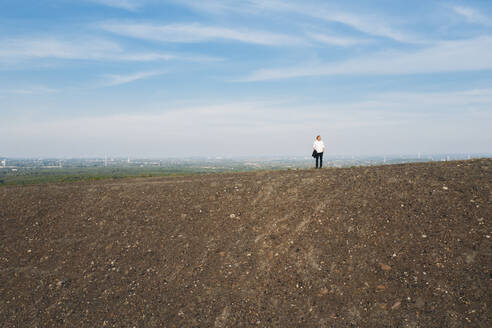 Businessman standing on hill against sky - MOEF02875