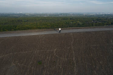 Businessman standing on hill against sky, drone view - MOEF02878