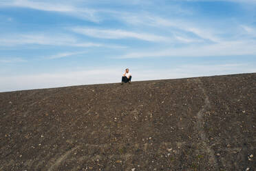 Mature businessman sitting on hill against sky - MOEF02881