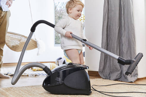 Cute toddler holding vacuum cleaner while standing on carpet by father at home - FSF01070