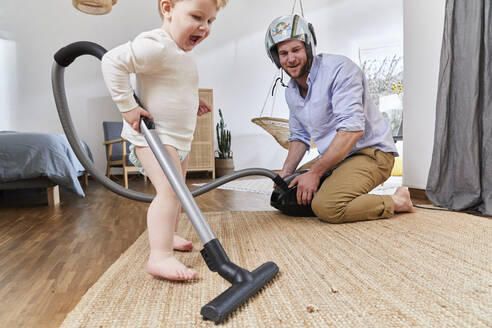 Cute baby boy cleaning carpet with vacuum cleaner by father in living room at home - FSF01073