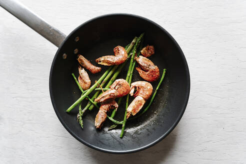 Overhead view of grilled prawns and asparagus on frying pan - JMHMF00042