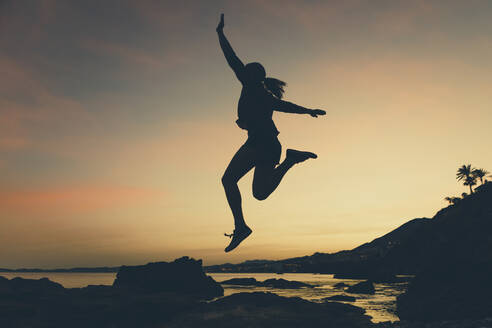 Silhouette of jumping woman at beach during sunset - DMGF00085