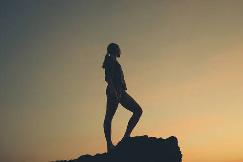 Woman standing on one leg at beach during sunset - DMGF00088