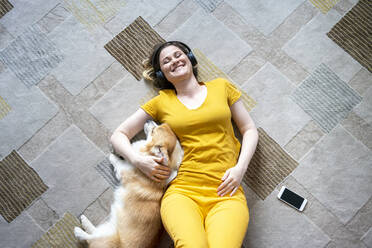 Happy woman with headphones cuddling with her dog in living room at home - VPIF02478