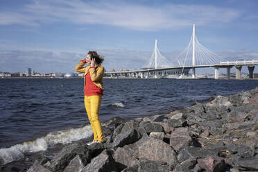 Woman standing at the coast listening to music, Saint Peterburg, Russia - VPIF02490