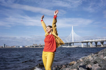 Carefree woman standing at the coastwith raised arms, Saint Peterburg, Russia - VPIF02493
