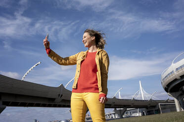 Happy woman with windswept hair taking a selfie at a road bridge - VPIF02496