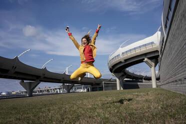 Carefree woman jumping at a road bridge - VPIF02499