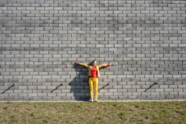Woman standing at a brick wall listening to music with headphones - VPIF02502